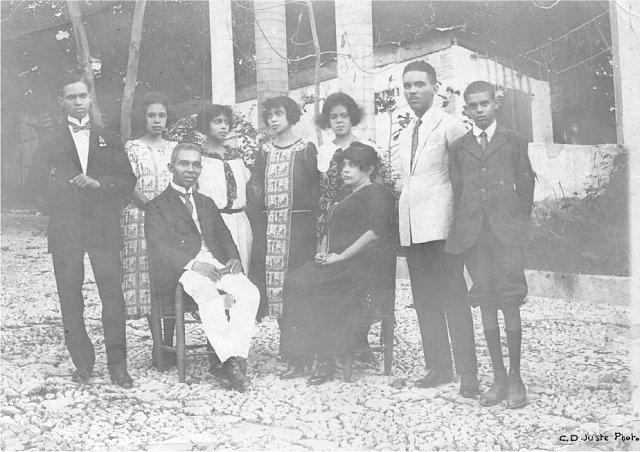 La famille Georges Sylvain, 1921 Assis, de gauche à droite: Monsieur Georges Sylvain (décédé en 1925) et Madame Sylvain (morte en décembre 1931). Derrière, les enfants (de gauche à droite): Henry, Yvonne, Jeanne, Suzanne, Madeleine (-Bouchereau), Normil et le cadet, Pierre. D.R. photo léguée par M. Jean Comhaire à K. Gyssels